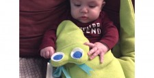 Baby boy with looking at the bright eyes of Al-the-Gator microwave heating pad from Maine Warmers