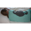 woman relaxing sore back muscles with a gray seal microwave heating pad