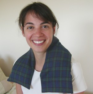 Woman using microwave heating pad for the neck in Black Watch plaid flannel to relax stiff muscles