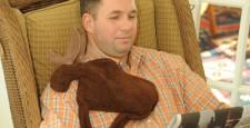 Man using Maine Warmers Moose microwave heating pad on stiff shoulder muscles