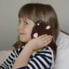 Young girl using mouse heat compress for ear aches