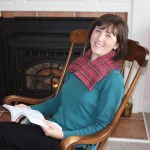 Woman relaxing with a Scotch red plaid microwave Neck Warmer in front of a fireplace
