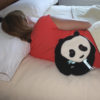 Woman relaxing back muscles with a Panda Bear microwave heating pad
