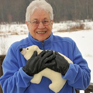 Woman using Polar Bear microwave heating pad to warm hands