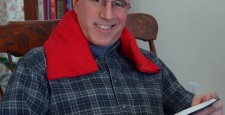 Man relaxing with red flannel neck warmer while reading