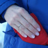 Small, red microwave hand warmer being inserted into a woman's coat pocket