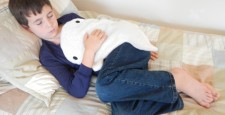 Boy sleeping with a white whale microwave heating pad