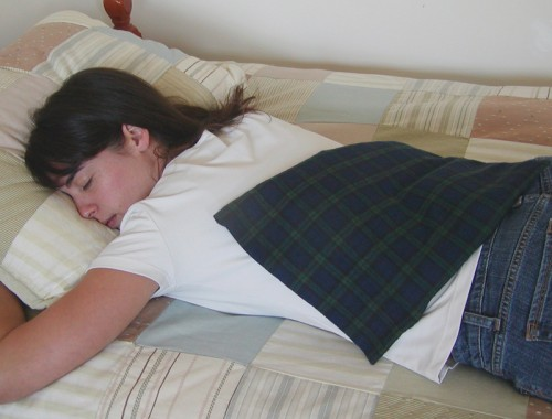 Woman relaxing tight back muscles with the best microwave heating pad in Black Watch plaid flannel