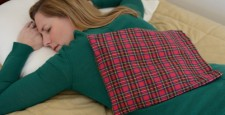Woman relaxing with a back heating pad in Scotch red plaid flannel