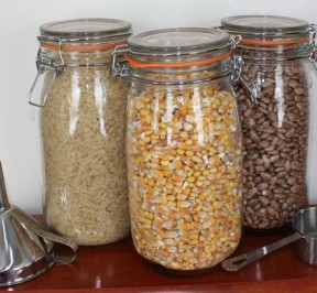 Three glass jars each filled with whole corn, whie rice, and dried Pinto beans for filling microwave heating pads