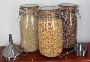 Three glass jars each filled with whole corn, white rice, and dried Pinto beans for filling microwave heating pads