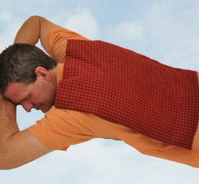 Man using extra large microwave heating pad to relax stiff back muscles, feeling great, and floating on some clouds