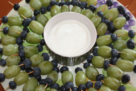 Green grapes and blueberries on toothpicks arranged  around a plate with yogurt dip in the center