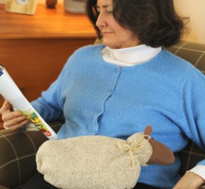Woman relaxing with a Cozy Sheep Heating Pad from Maine Warmers