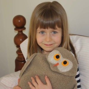 Young girl using owl microwave heating pad for comfort while dealing with juvenile arthritis