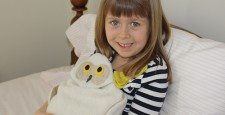 Girl using Snowy Owl bed warmer
