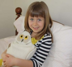Girl using Snowy Owl microwave heating pad to ease a tummy ache