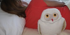 Woman using Maine Warmers Snowy Owl heating pad on her back while lying on her side