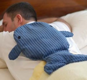 man using whale shaped microwave heating pad to help relax back muscles before surgery