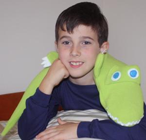 Boy using alligator microwave heating pad for arthtitis