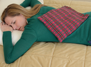 Woman relaxing stiff back muscles with a microwave heating pad in Scotch plaid flannel