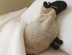 Sheep microwave heating pad warming a bed
