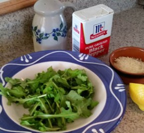 Arugula salad for one with salt & pepper shakers, half a lemon, and grated parmesan