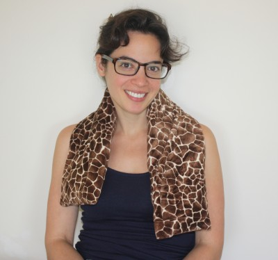 Woman relaxing with an extra long neck warmer in giraffe print extra soft plush