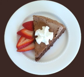 Wedge of Flourless Chocolate Cake with sliced strawberries on the side and a little whipped cream on top