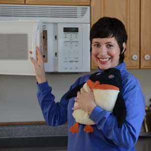 Woman warming hands on a Penguin microwave heating pad that just came out of the microwave oven