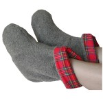 Someone resting their feet with a pair of gray foot warmers with Scotch red plaid lining that are microwaveable