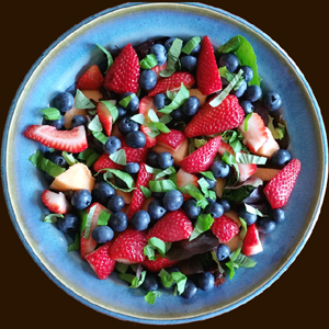 Fresh Blueberries_ strawberries_ cantaloupe_ and basil on fresh baby greens in a blue pottery salad bowl