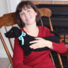 Woman relaxng with black dachshund microwaveable neck wrap